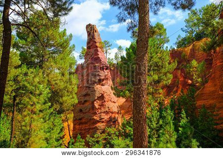 Roussillon Ochre Deposit: Beautiful Big Red Ocher Peak, Blue Sky With Clouds And Green Pines.