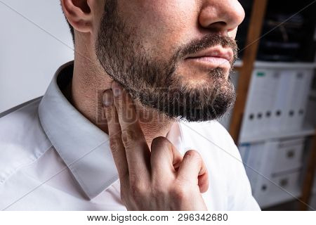 Close-up Of Young Man Touching His Neck To Eliminate High Blood Pressure poster