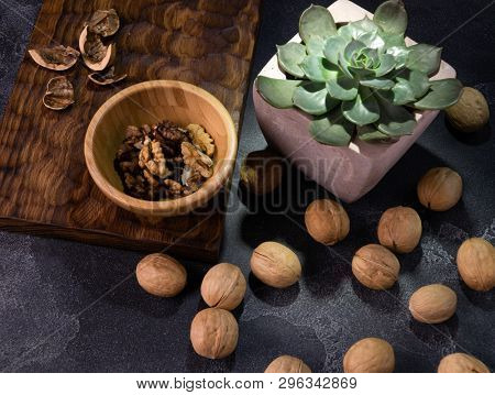 Walnut kernels in wooden bowl, whole walnuts and Echeveria plant on blue slate table. Healthy nuts and seeds composition.