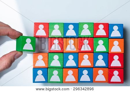 Businessperson's Hand Holding Green Cubic Block