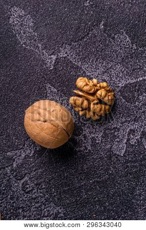 Walnut kernel and whole walnut on blue slate surface. Healthy diet composition.