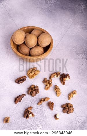 Walnuts in wooden bowl on bright textured surface, top view. Healthy nuts and seeds composition.