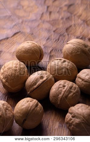 Whole walnuts lying on carved wooden board, top view. Healthy nuts and seeds composition, background.