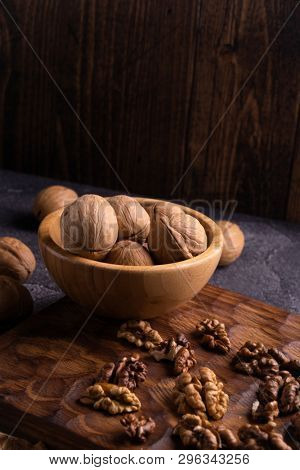 Walnuts in wooden bowl on wooden carved board, side view. Healthy nuts and seeds composition.