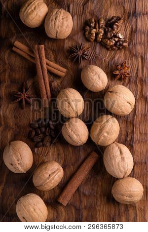 Walnuts, cinnamon, anise, and coffee beans on wooden cutting board. Nuts and spices on the table. Food composition, top view.