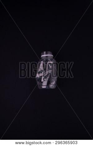 Squashed plastic bottle on black background. Plastic utilisation concept. Ecological problem, global environment.