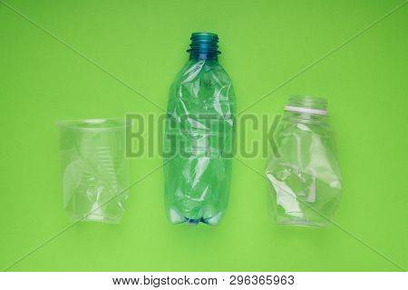 Squashed plastic bottles and a cup on bright green background. Plastic utilisation concept. Ecological problem, global environment.