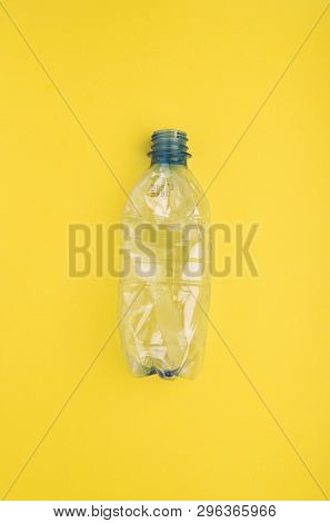 Squashed plastic bottle on yellow background. Plastic utilisation concept. Ecological problem, global environment.