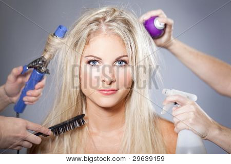 Beautiful woman surrounded by hair care tools