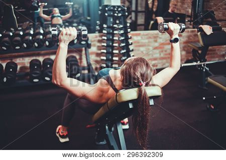 Young Woman Doing Exercise With Dumbbells For The Muscles Of Chest And Shoulders On Inclined Bench I