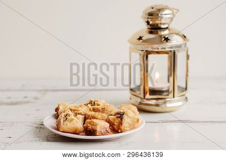 Plate With Arabic Baklava And Lantern With Burning Candle On Wooden Table. Ramadan Concept