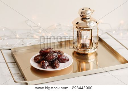 Dried Dates On White Plate Served In A Metal Tray With Golden Lantern With Burning Candle, Lights As