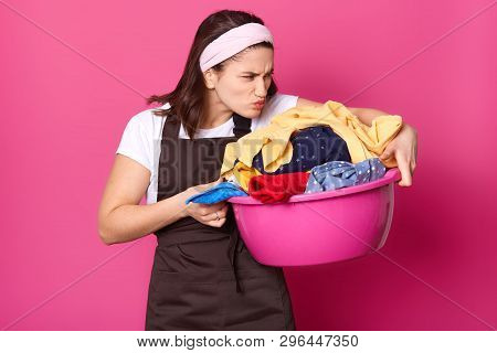 Indoor Shot Of Young Tired Housewife, Doing House Chores, Smelling Dirty Clothes, Going To Wash Them