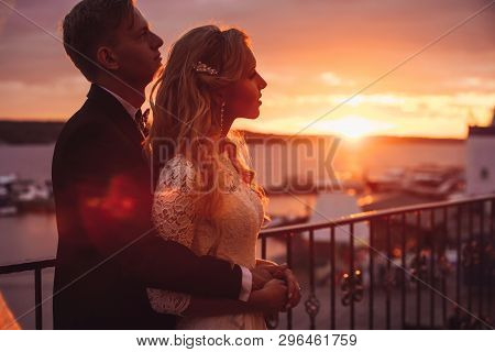 Wedding Couple Gently Hugging And Looking Into The Distance, Towards The Sea. Young Attractive Man A