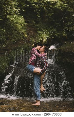 Beautiful Young Couple Kisses Against The Backdrop Of An Amazing Waterfall. Man And Woman Are Dresse