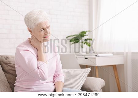 Mature Woman Suffering From Backache At Home, Massaging Neck With Hand, Feeling Exhausted, Empty Spa