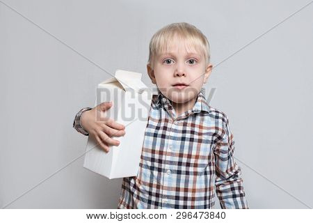 Little Blond Boy Cuddles A Large White Carton Package. Light Background.