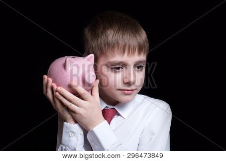 Boy Listens Attentively To The Pink Piggy Bank. Business Concept. Black Background