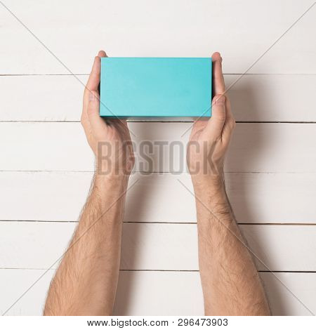 Rectangular Turquoise Box In Male Hands. Top View. White Table On The Background
