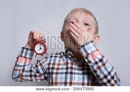 Yawning Little Blond Boy With A Red Alarm Clock In His Hands. Morning Concept. Light Background