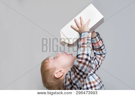 Little Blond Boy Drinks From A Large White Package. Light Background.