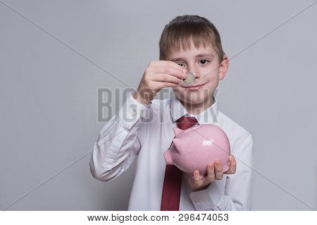 Smiling Boy Puts A Coin In A Pink Piggy Bank. Business Concept. Light Background