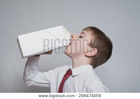 Little Boy Drinks From A Large White Package. White Shirt And Red Tie. Light Background.