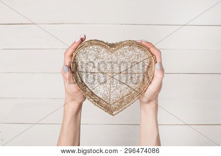 Female Hands Hold Metal Wire Transparent Heart Shaped Box Against The Background Of A White Wooden T