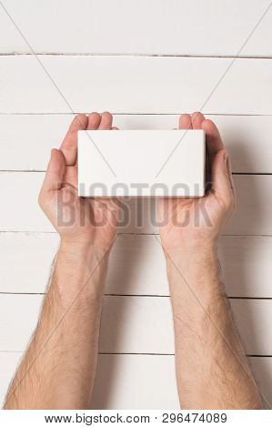 White Rectangular Box In Male Hands. Top View. White Table On The Background