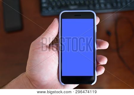 Male Hand With A Smartphone. Black Blank Screen. Home Background