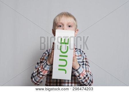 Little Blond Boy Is Holding A Big White Carton Juice Package. Light Background.