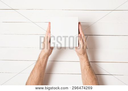 Small White Cardboard Boxes In Male Hands. Top View. White Table On The Background