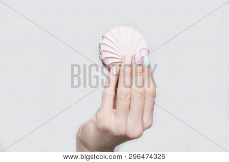 Female Hand With A Gentle Manicure On A White Wooden Background. Marshmallow In The Hands