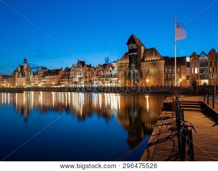 Old Town In Gdansk, Poland At Night. Riverside With The Famous Crane And City Reflections In The Mot
