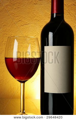 Glass and bottle of red wine with blank label