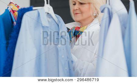 Senior Fashion. Stylish Showroom. Elegant Aged Lady Looking Through Rack Of Clothing. Shopping Leisu