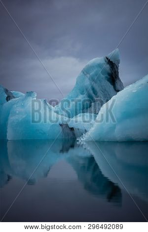 Large Vertical Blue Glaciers Reflecting On Calm Waters In The Artic.