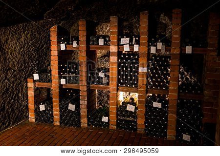 Old Aged Traditional Wooden Barrels With Wine In A Vault Lined Up In Cool And Dark Cellar In Italy,