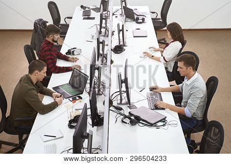 Young Professionals Working In Modern Office. Group Of Developers Or Programmers Sitting At Desks Fo