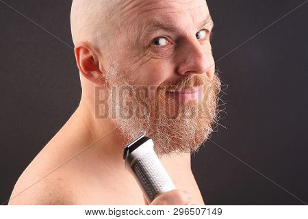 Bearded Man With Trimmer To Adjust Beard In Hand