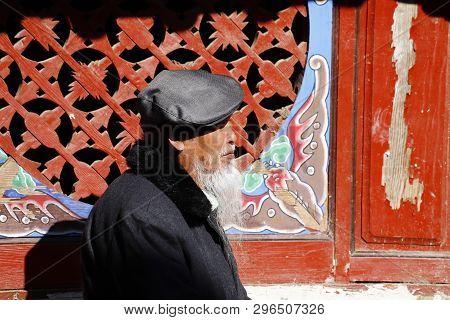 Shigu, Yunnan, China - November, 2018. An Elderly Chinese Man With A Characteristic Beard Along The