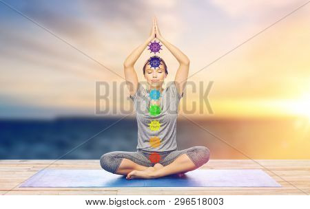 mindfulness, spirituality and outdoor yoga - woman meditating in lotus pose with seven chakra symbols over sea and sunlight background