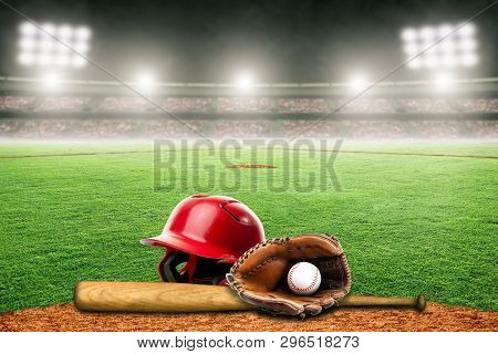Baseball Helmet, Bat, Glove And Ball On Field At Brightly Lit Outdoor Stadium. Focus On Foreground A