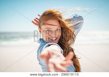 Cheerful young woman with red hair enjoying holiday at beach. Beautiful mature woman at sea during a windy day. Attractive girl smiling and looking at camera while feeling free at beach.