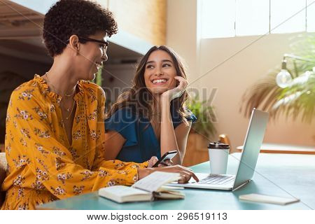 Happy college friends sitting in a conversation while working on project. Two women studying together at library. Happy brazilian girl with smart phone and smiling woman chatting at cafeteria.