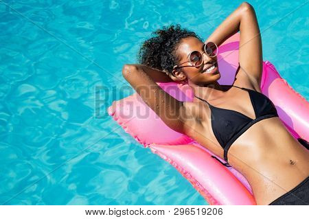 Beautiful african woman lying on pink mattress in outdoor swimming pool. Young black woman sunbathing in swimming pool with copy space. Happy girl in glamour bikini relaxing in pool with eyeglasses.