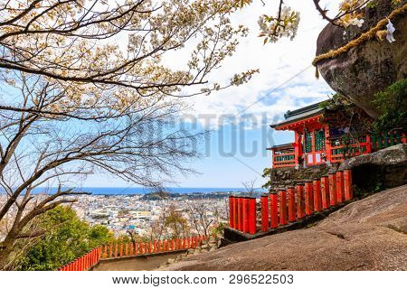 The Kamikura Shinto shrine at the top of a hill against a large rock boulder, Shingu, Japan