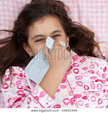 Portrait of a beautiful hispanic girl sick with the flu and covering his nose with a handkerchief laying in a bed with pink sheets