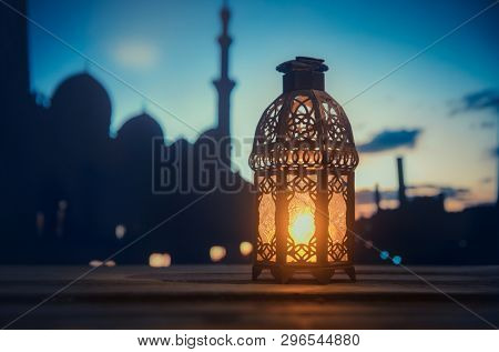 Ramadan Kareem greeting photo with serene mosque background with beautiful glowing lantern.