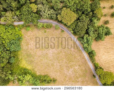 Top Down Aerial View Of French Countryside With Rural Road, Meadows, Forest And Natural Woodland Edg